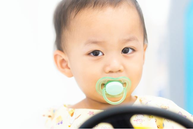 Childbaby boy driving toy car at hospital